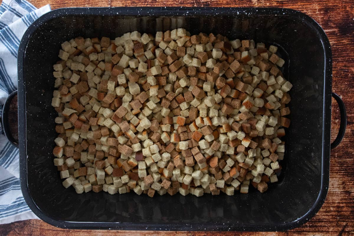 Bread cubes being shown in a large roasting pan that is sitting on top of a wooden countertop.