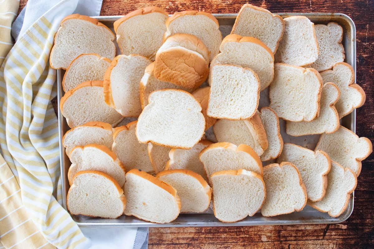 Slices of white bread spread out on a baking sheet.