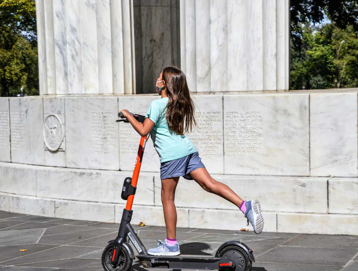 Tween girl on powered scooter wearing a face mask.