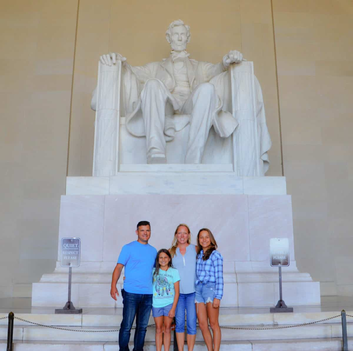 A white family with two teen daughters in front of the Lincoln statue in Washington DC.
