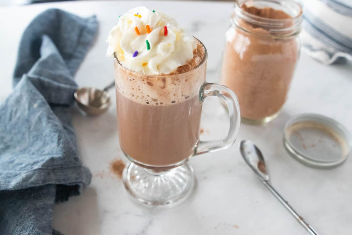 A glass mug being shown filled with hot chocolate and whipped cream. A blue dish towel, jar of hot chocolate mix and a tablespoon sit next to the mug all on top of a countertop.
