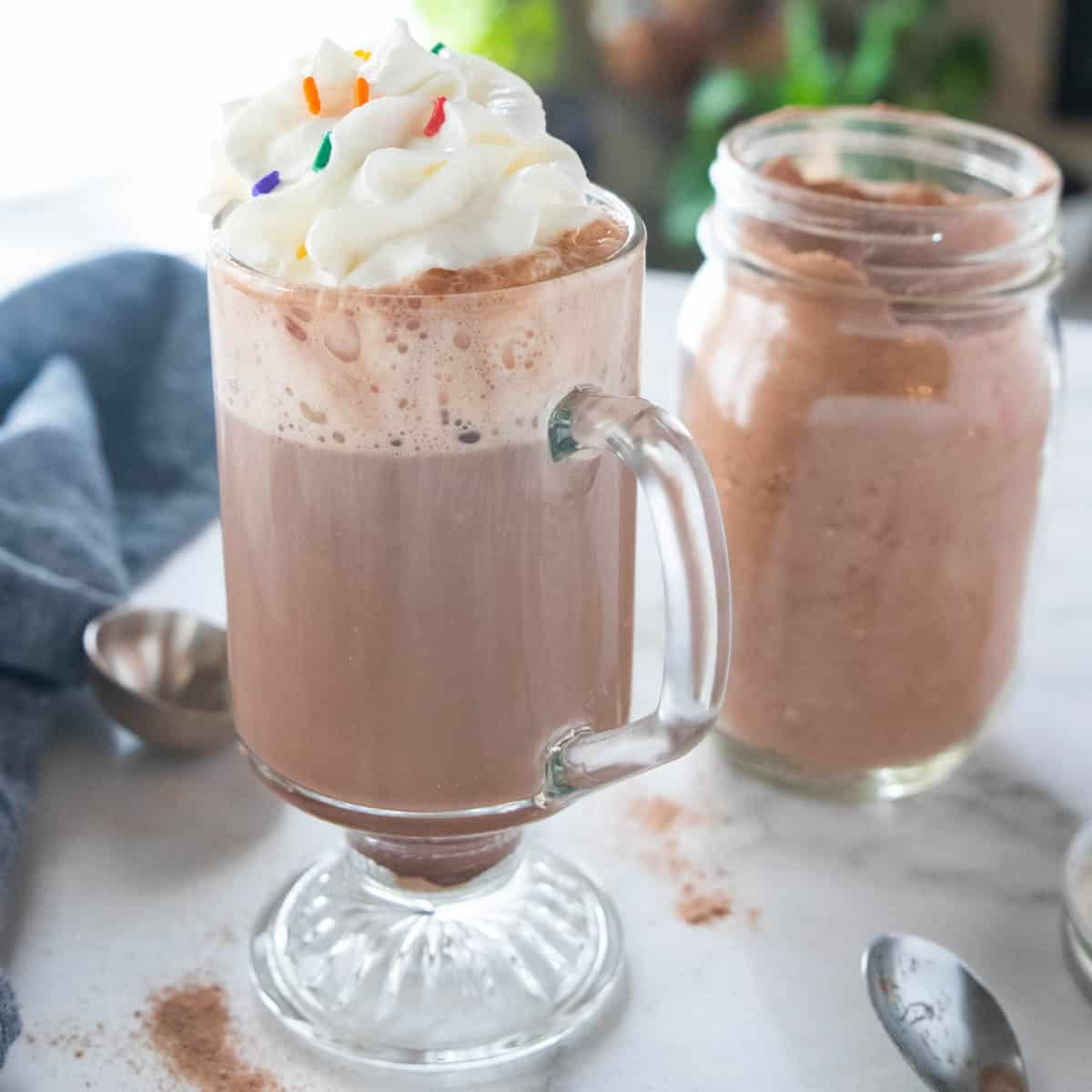 A glass mug filled with hot chocolate and topped with whipped cream sits on a countertop with a mason jar filled with hot chocolate mix behind the mug.