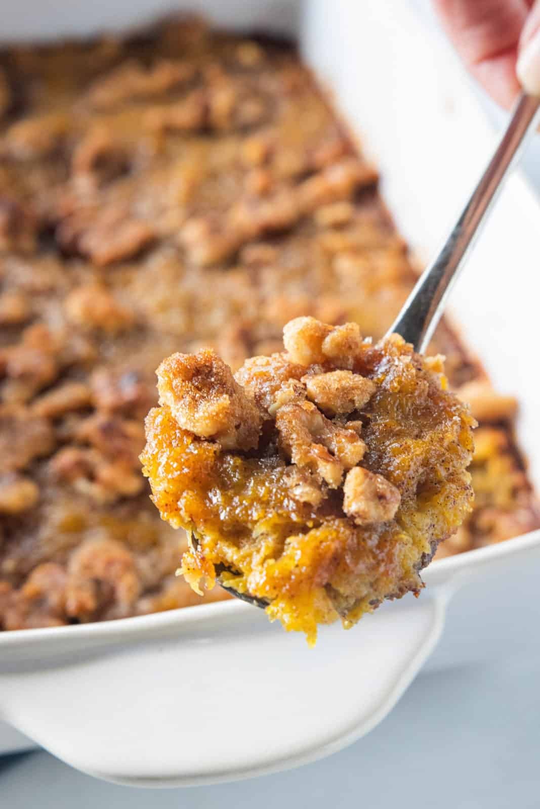Butternut squash casserole in a white baking dish with a spoon scooping a serving from the dish.