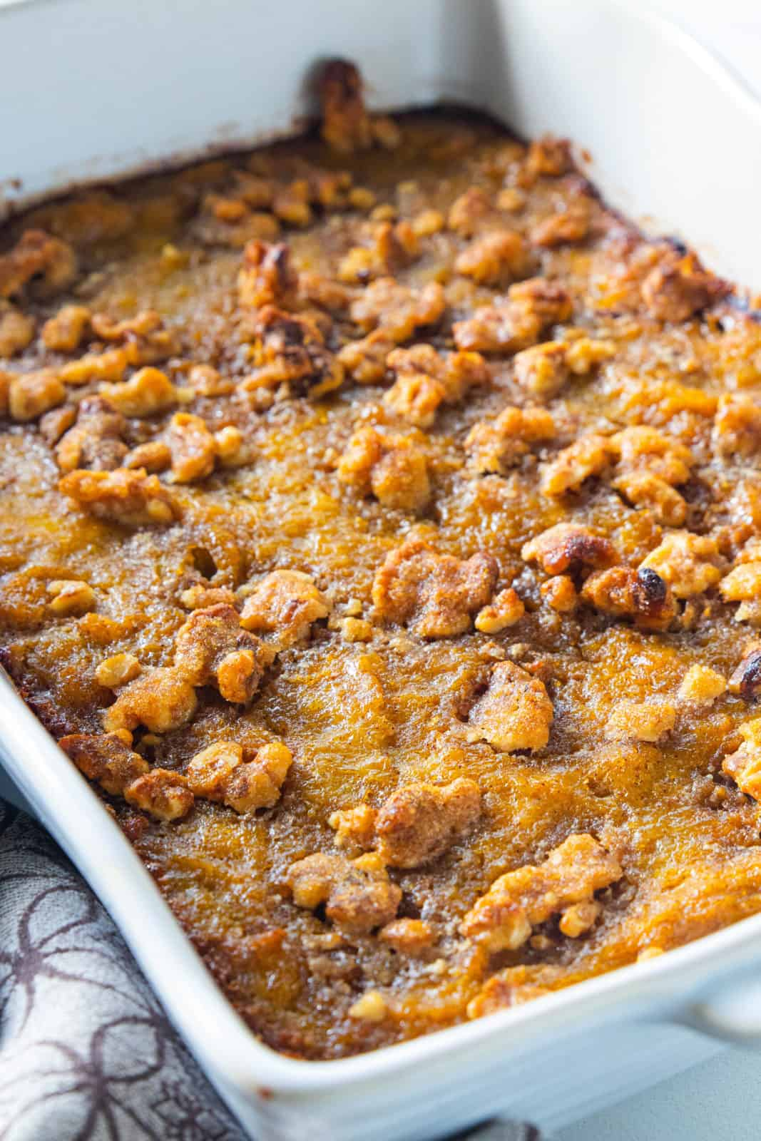 A white casserole dish filled with butternut squash casserole topped with roasted walnuts.
