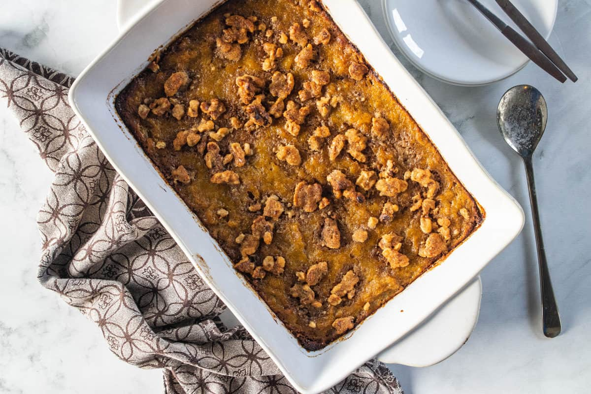 A top down view of a white pan with sweet potato casserole out of the oven next to a serving spoon and kitchen towel.