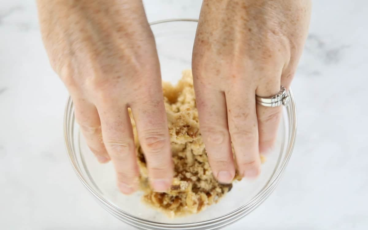 Hands mixing together the ingredients for crumb topping in a glass bowl.