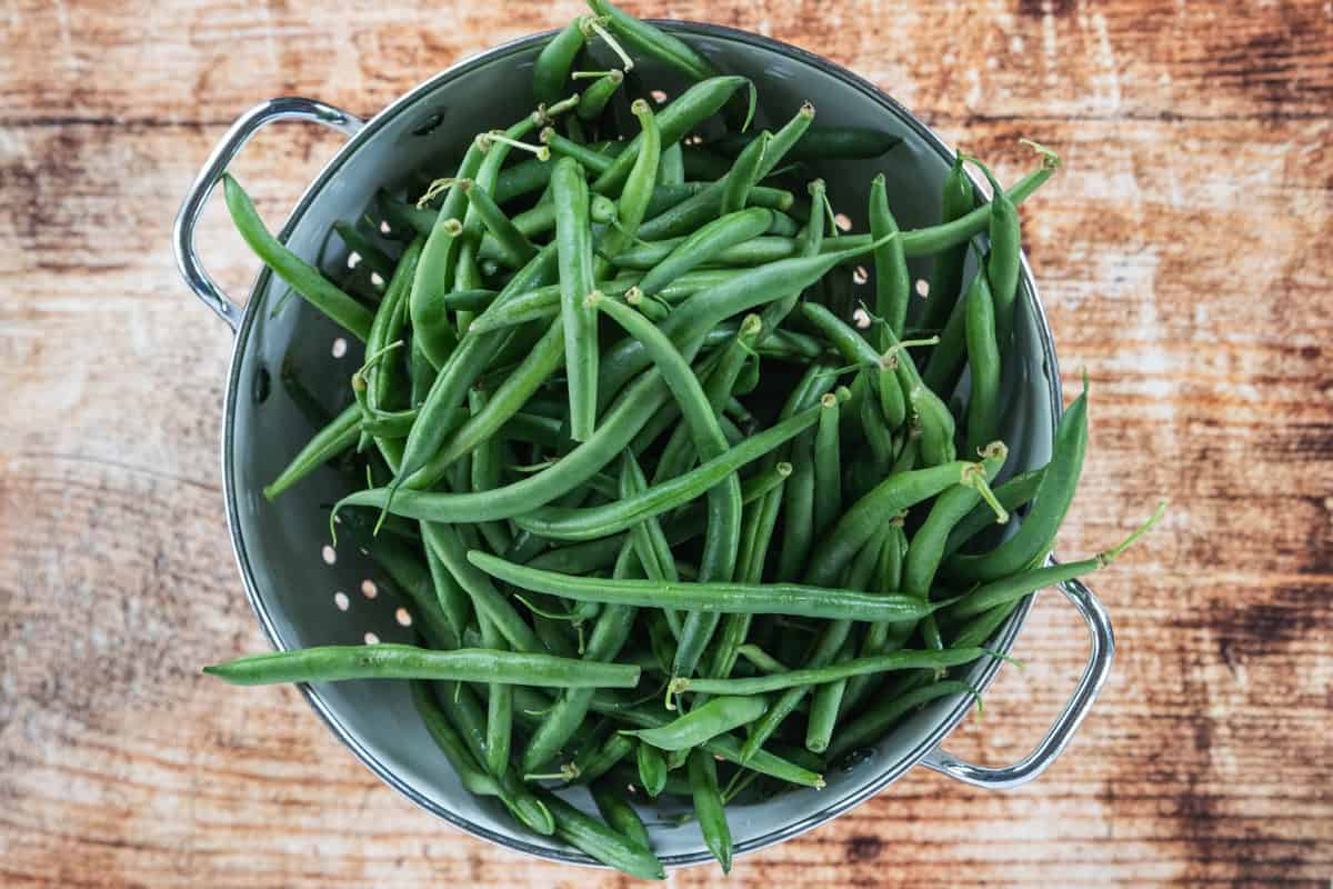 Fresh green beans in a colander that is on top of a wooden countertop.