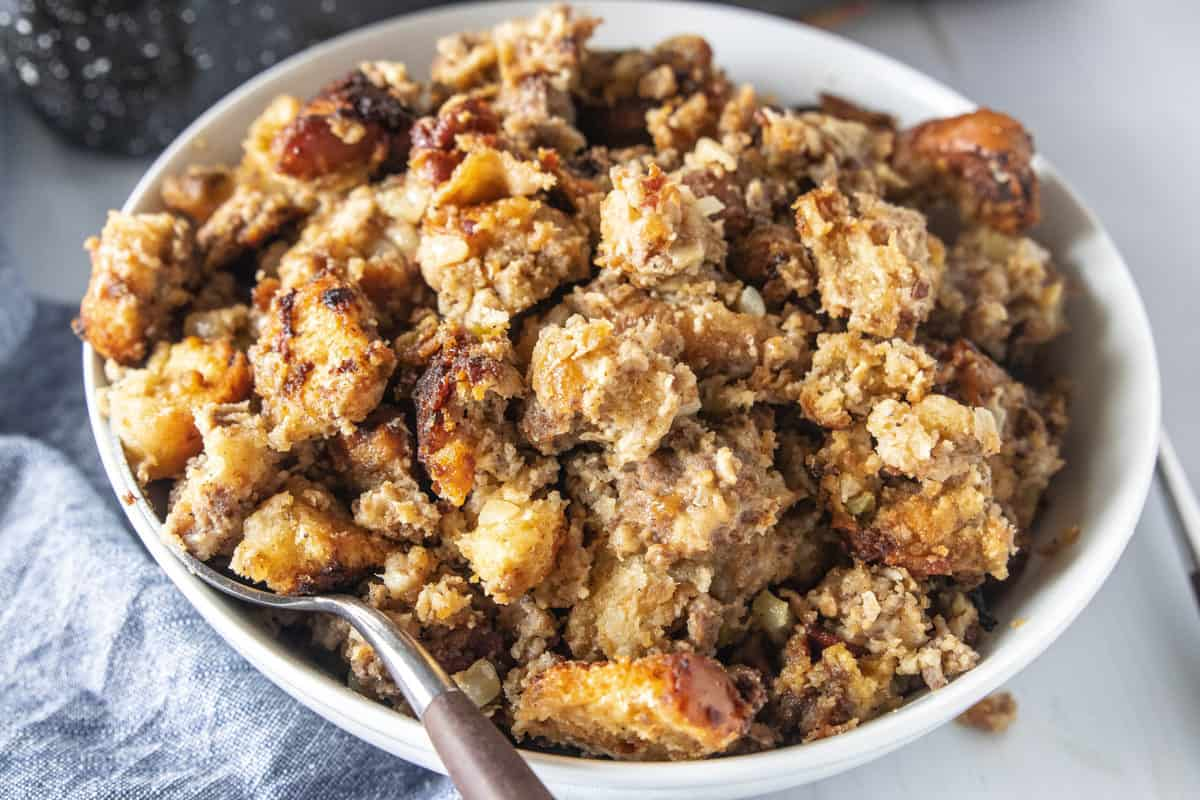 Stuffing in a white serving bowl with a spoon in the bowl.