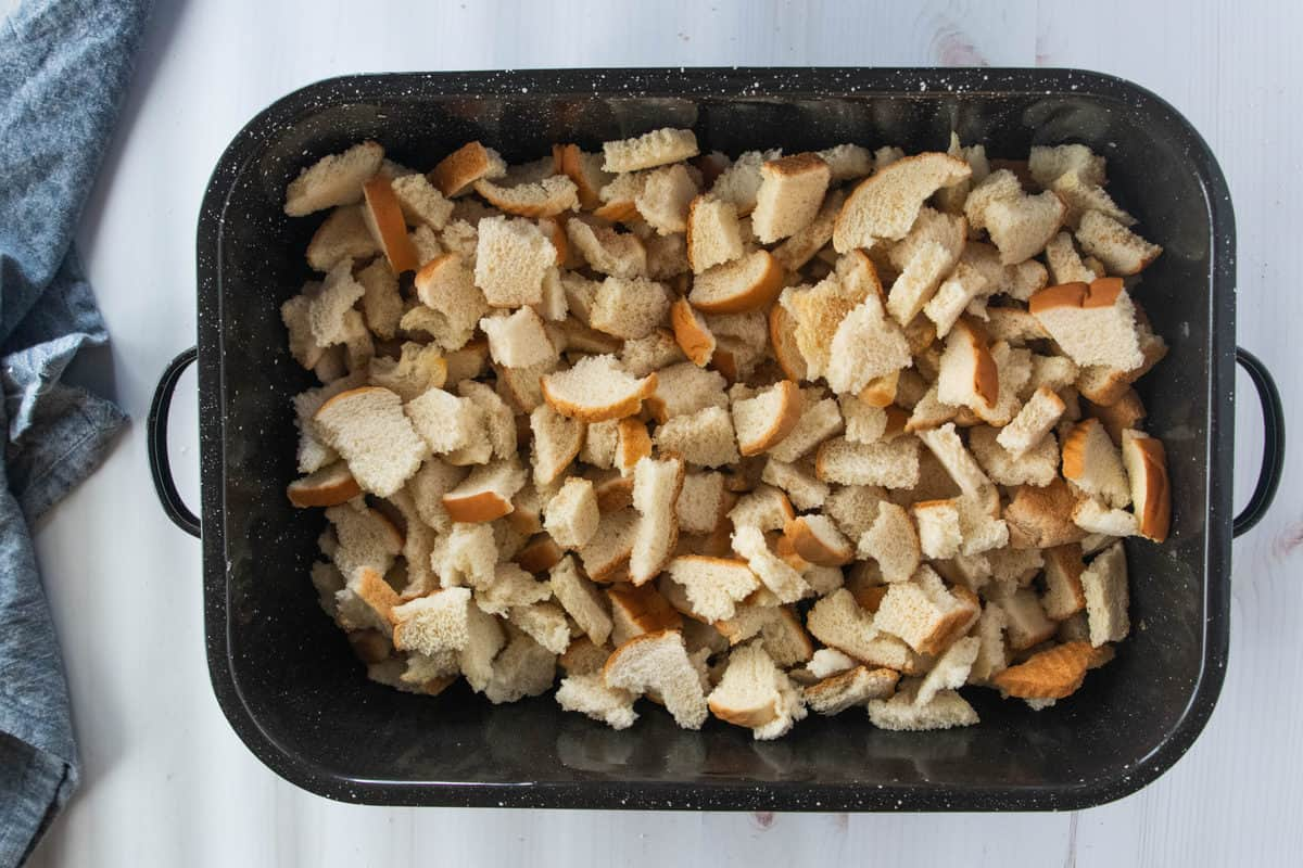 Pieces of torn white bread in a large baking pan.