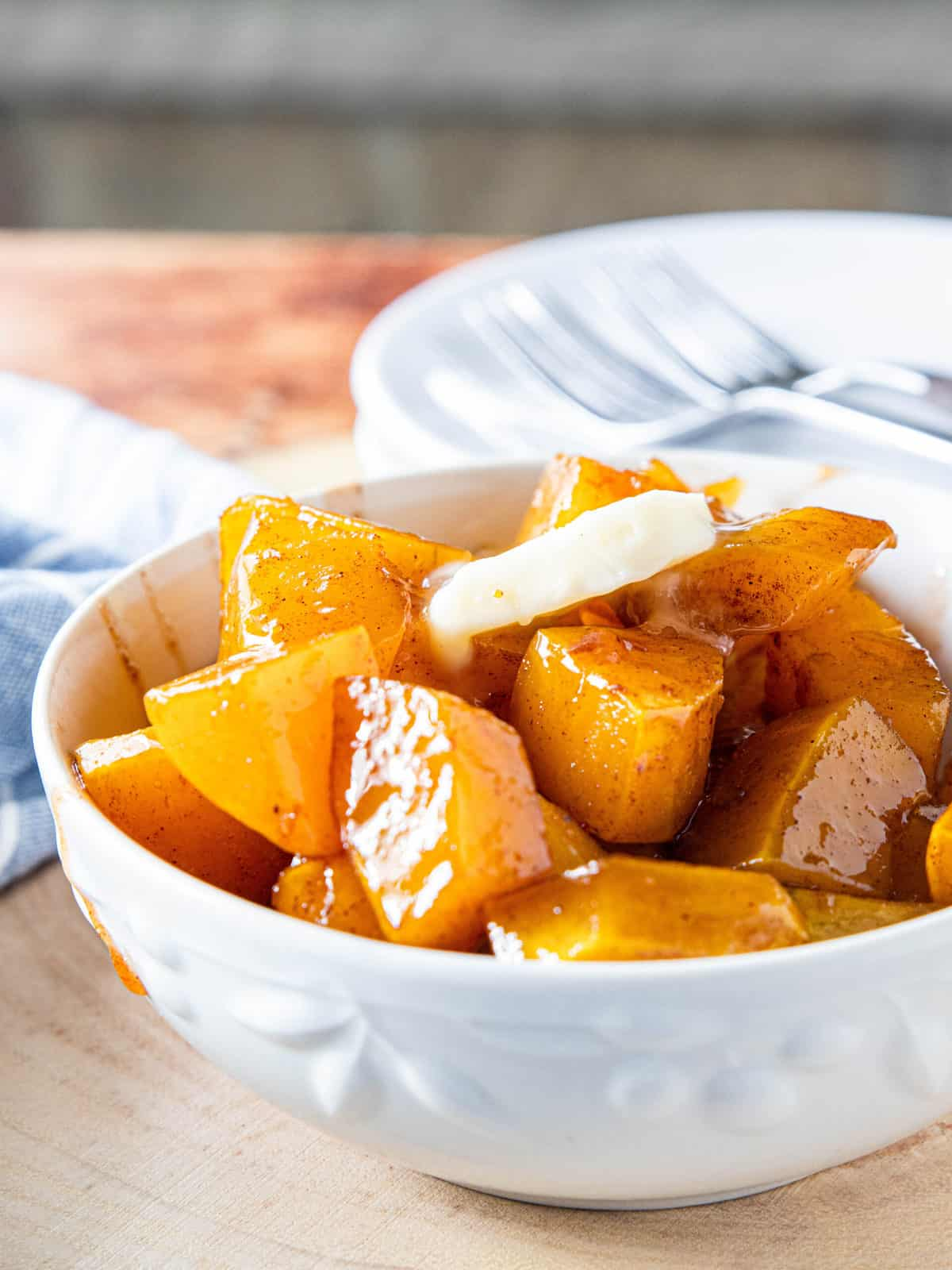 Maple roasted butternut squash in a white serving bowl.