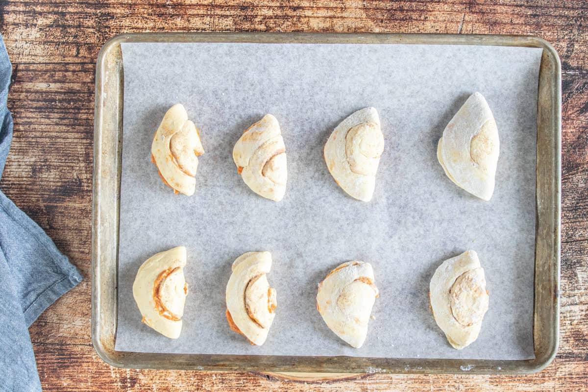 Unbaked pumpkin empanadas on a parchment lined baking sheet.