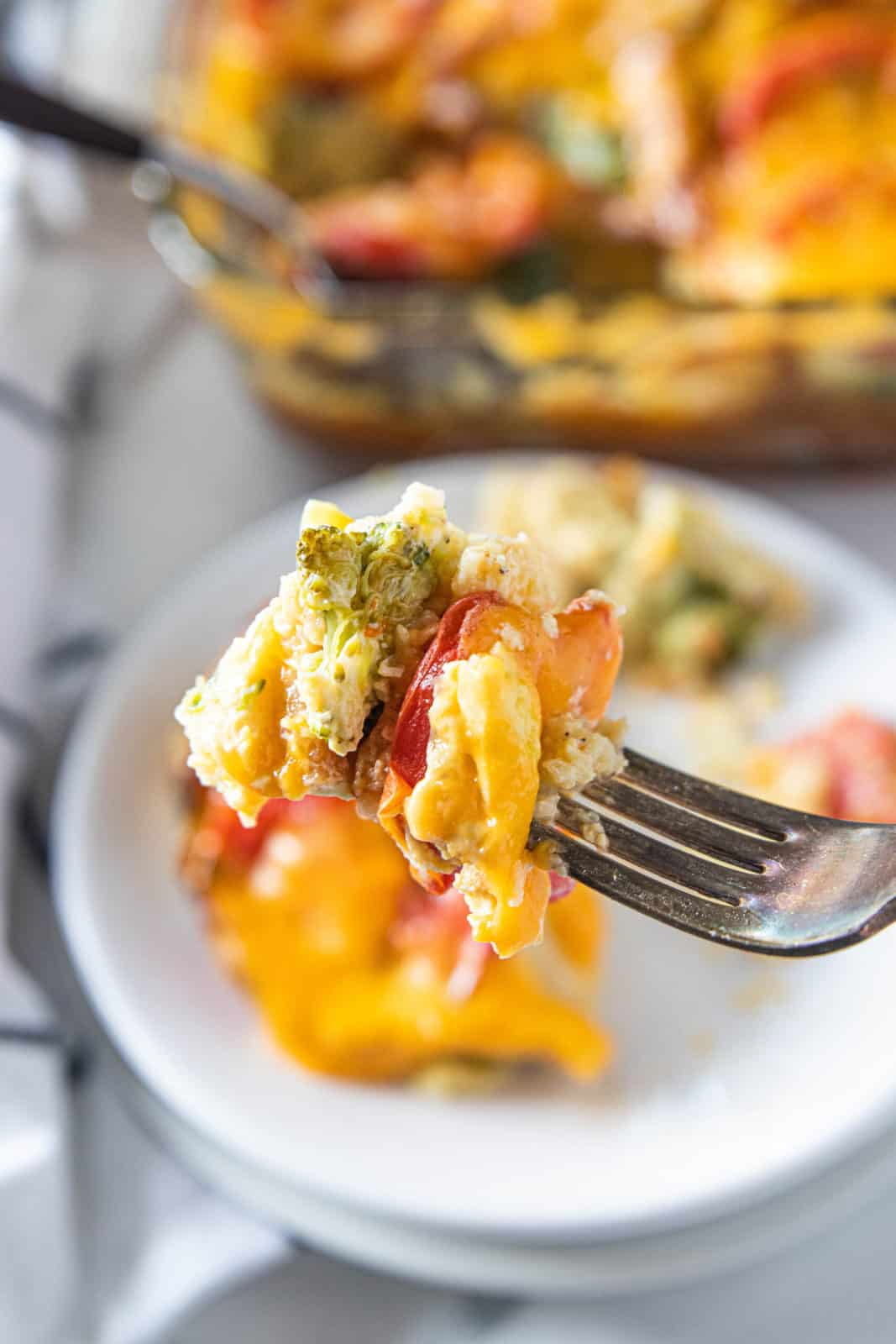 A fork being shown picking up a bite of vegetable strata from a plate.