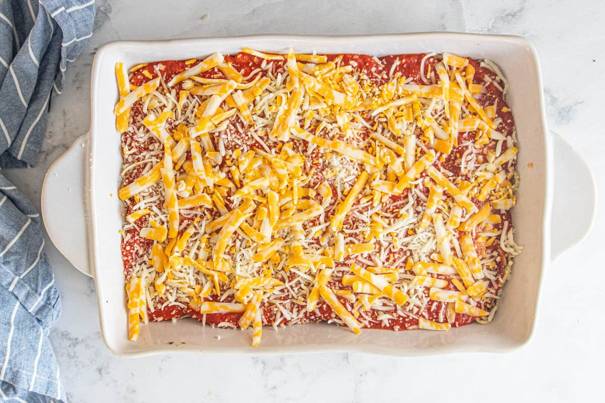 Vegetarian baked spaghetti being shown prior to being baked in a large baking dish with shredded cheese on the top.