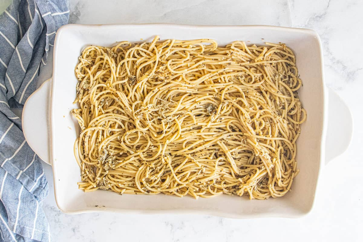 Cooked spaghetti tossed in spices being shown in a large white baking pan