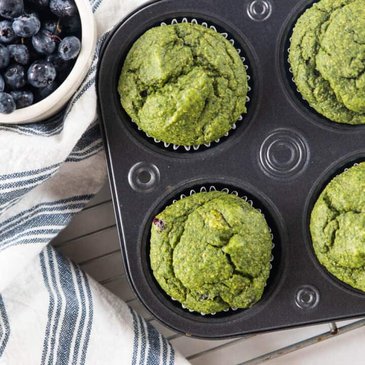 spinach blueberry muffins in a muffin tin.