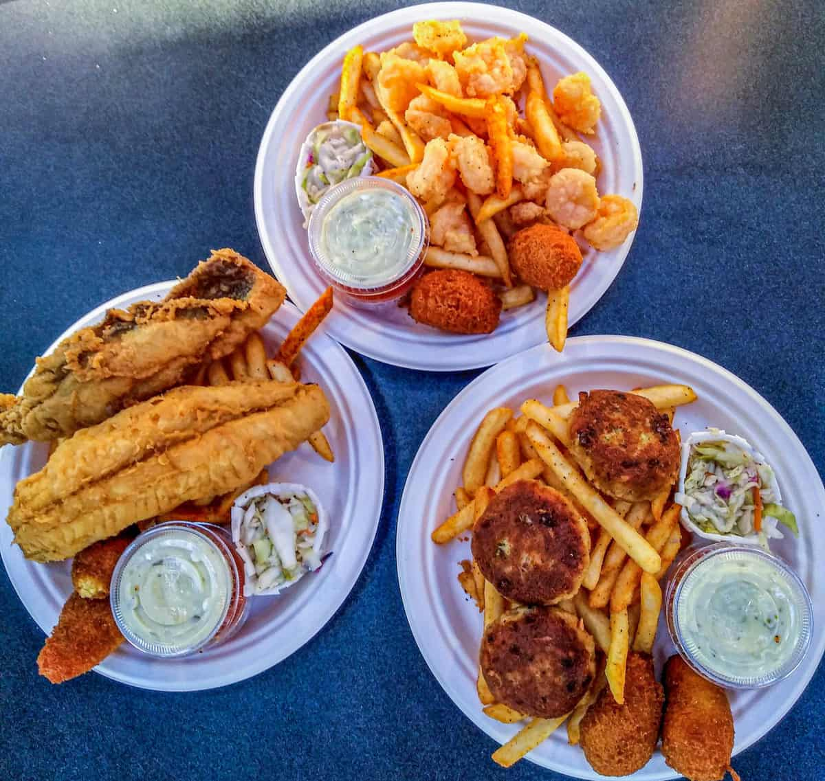 Three plates of fried seafood with sides in Charleston NC.