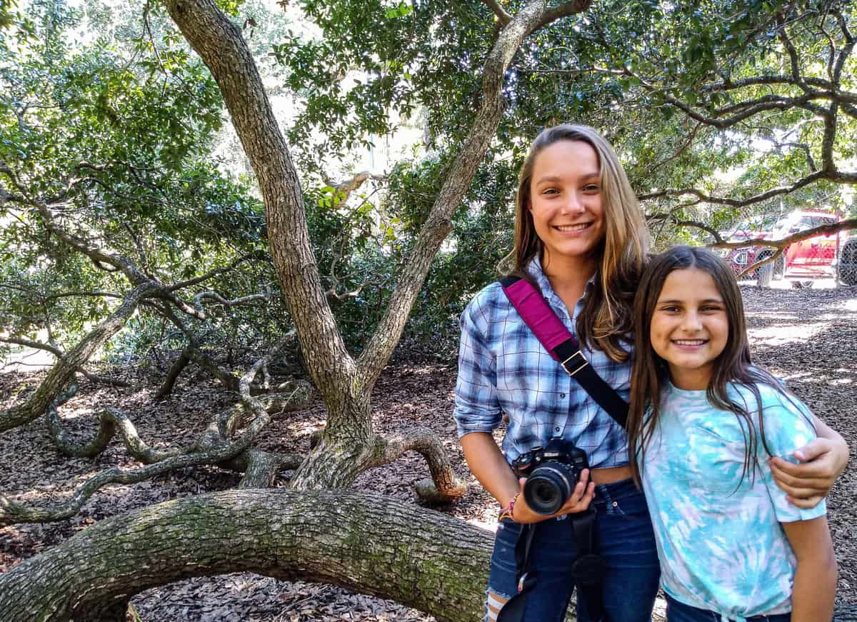 Teen girls standing in from of large trees with a camera in Charleston NC.