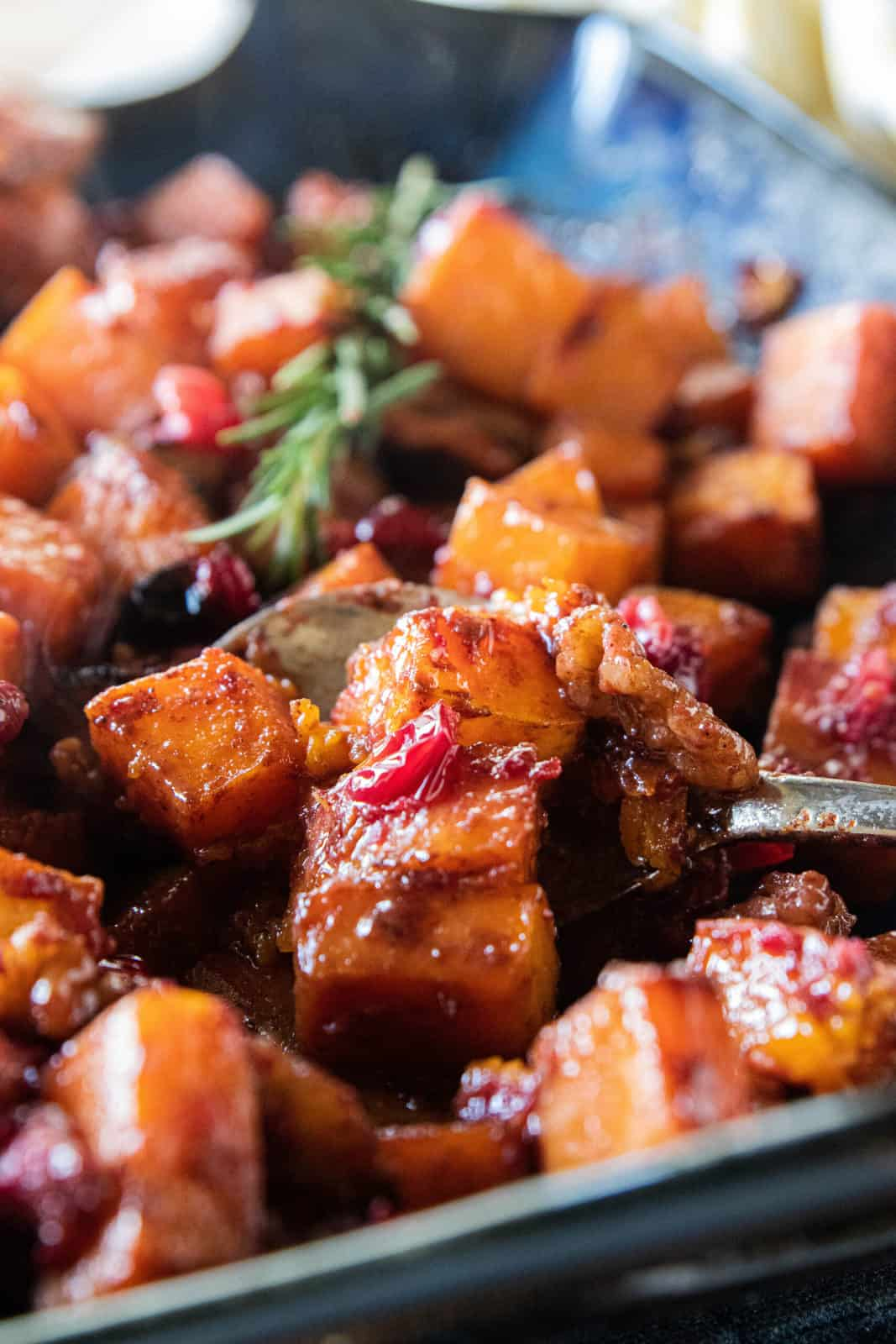 A spoon being shown scooping up a serving of roasted butternut squash with walnuts and cranberries in a baking dish.
