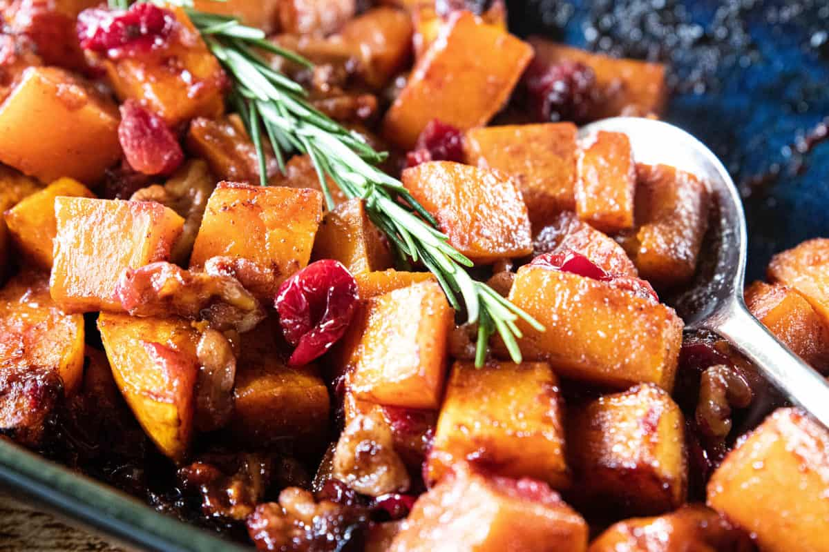 Roasted Butternut Squash with Cranberries and Walnuts being shown in a baking dish.