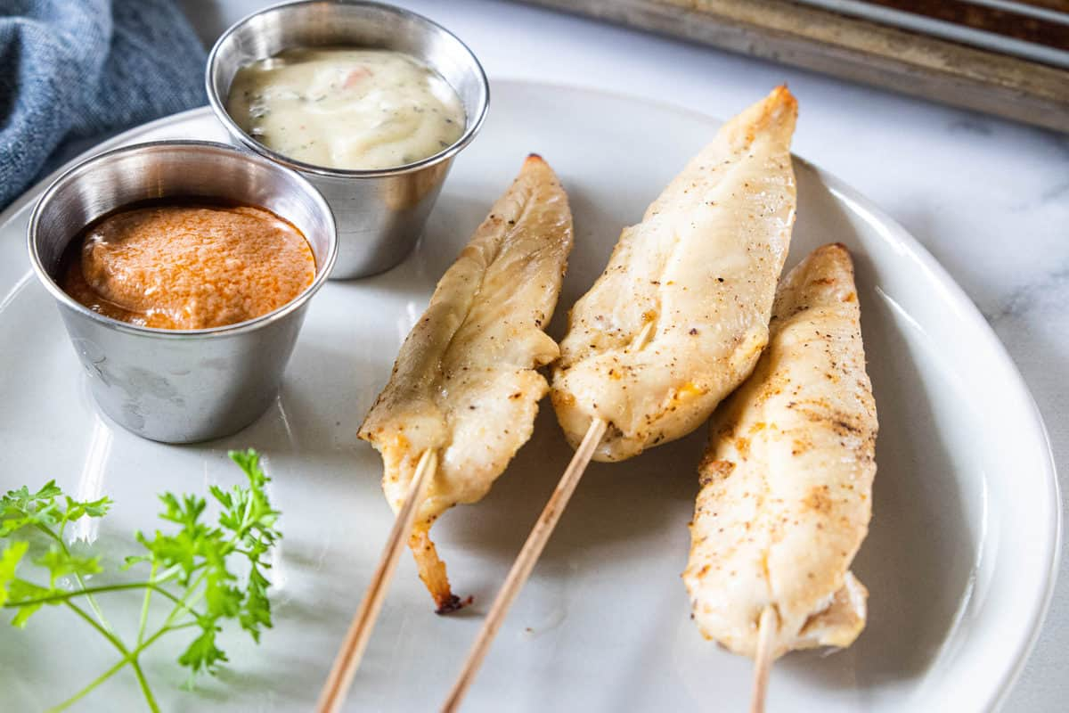Chicken sticks being shown on a white plate with two ramekins on the plate filled with dipping sauces.