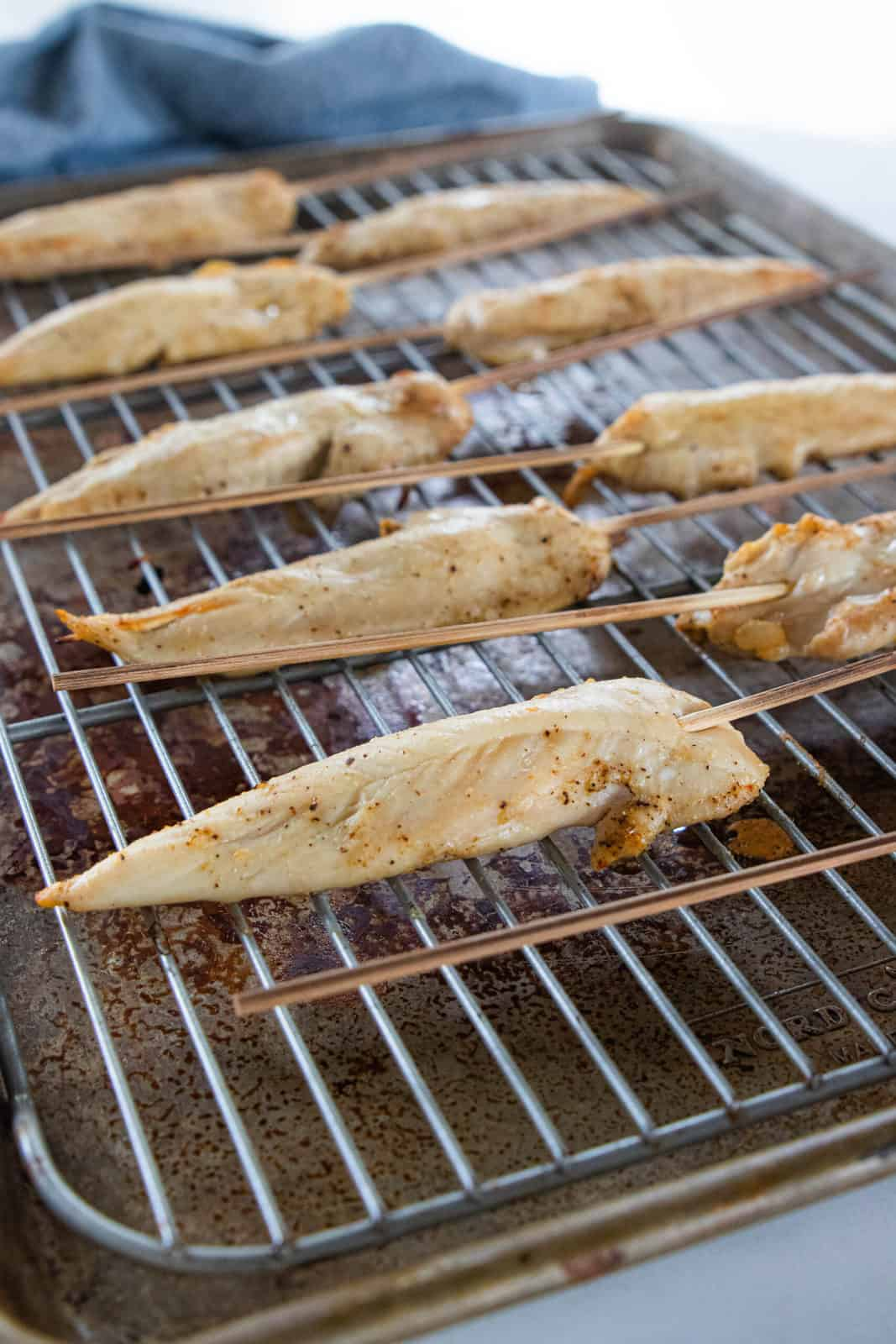 Chicken sticks being shown on a baking sheet.