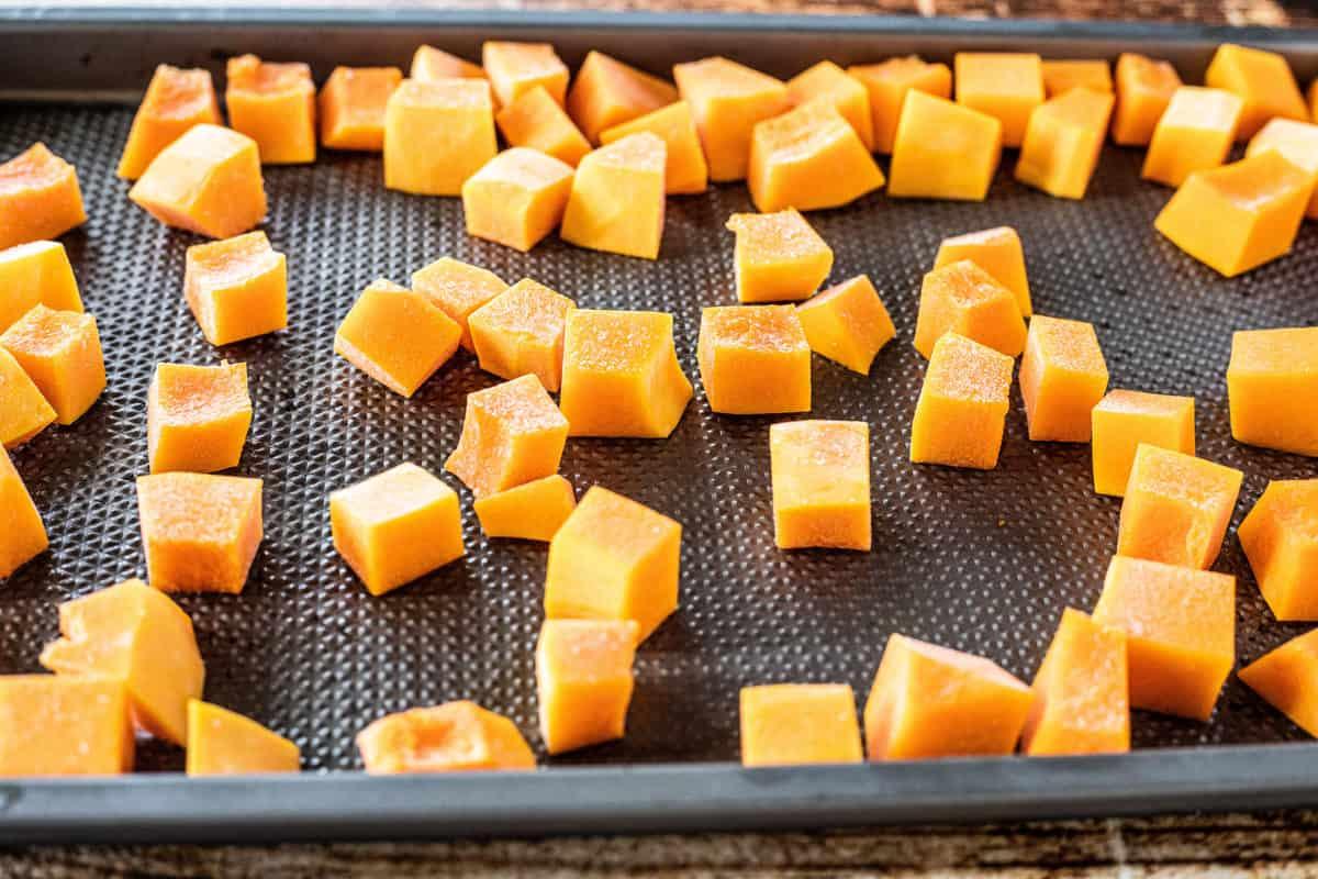 Chopped butternut squash on a baking sheet.