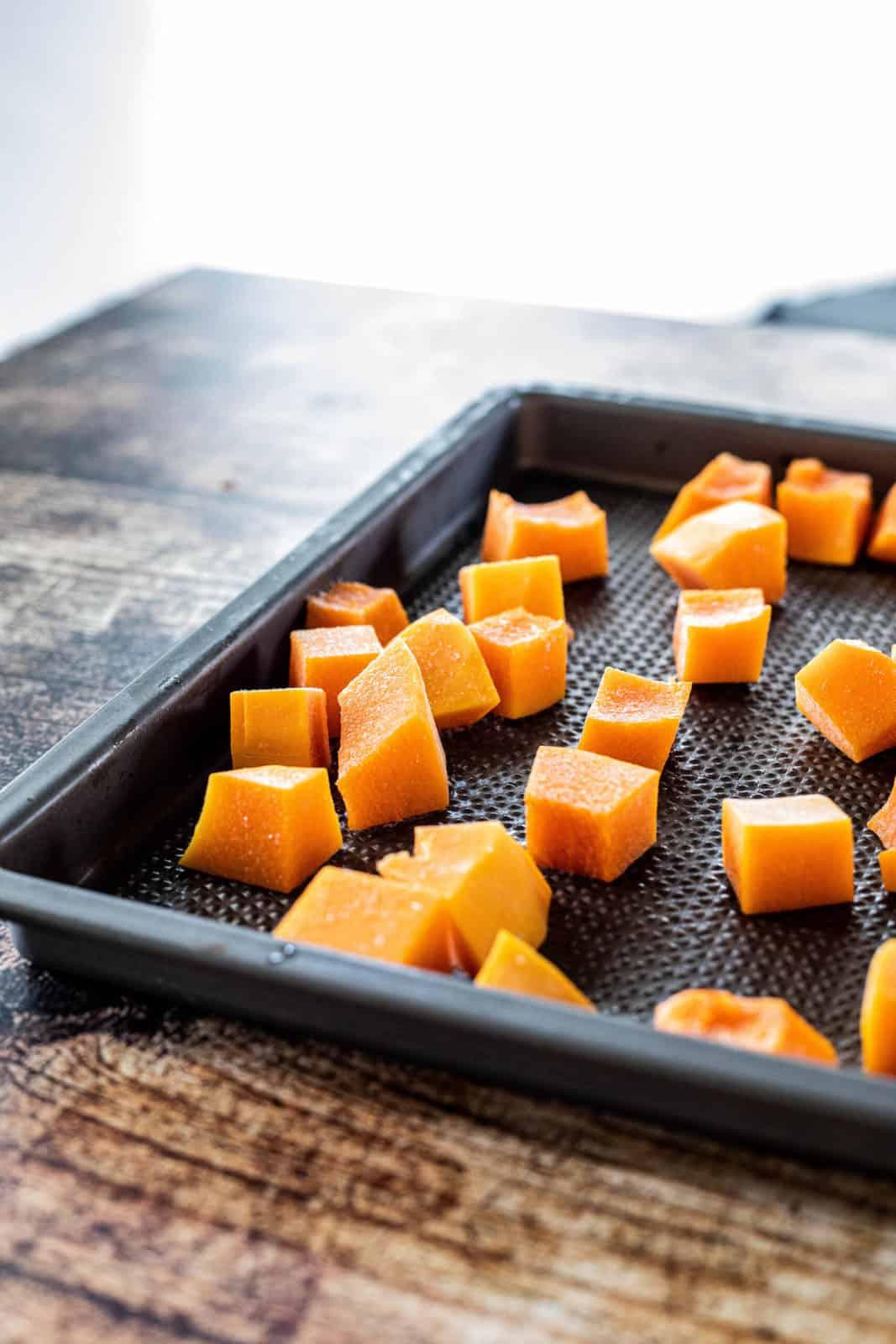 Cut butternut squash on top of a baking sheet.