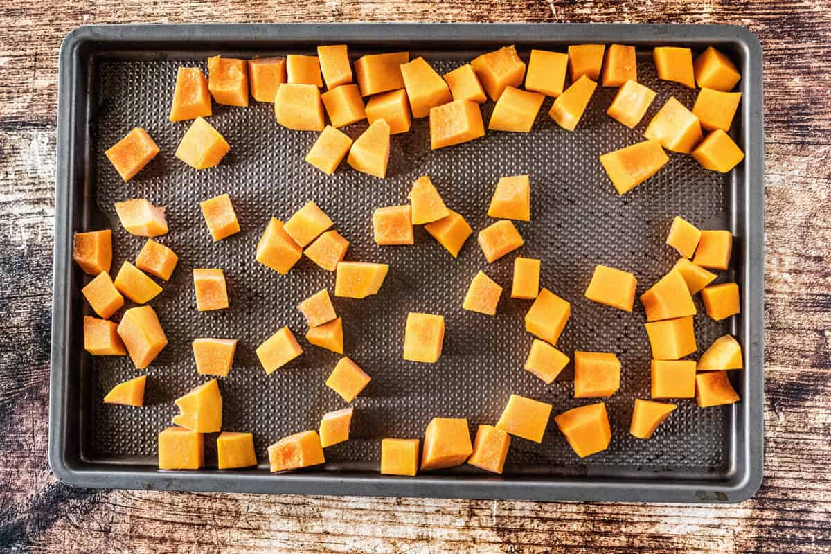 Butternut squash that has been chopped and added to a baking sheet that is on top of a wooden countertop.