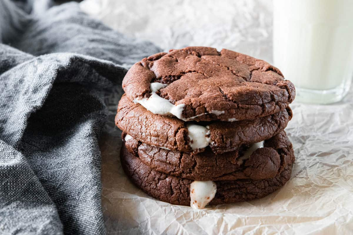 A stack of chocolate marshmallow cookies being shown on top of a piece of parchment paper with a dish towel next to the cookies.