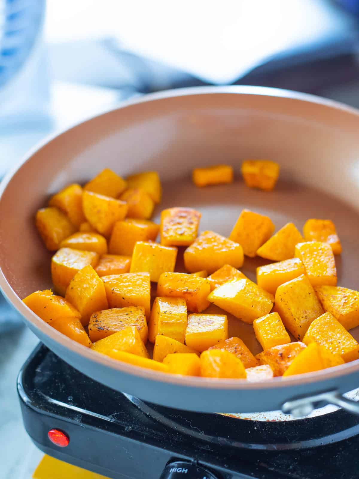 Chopped squash being shown in a medium sized skillet.