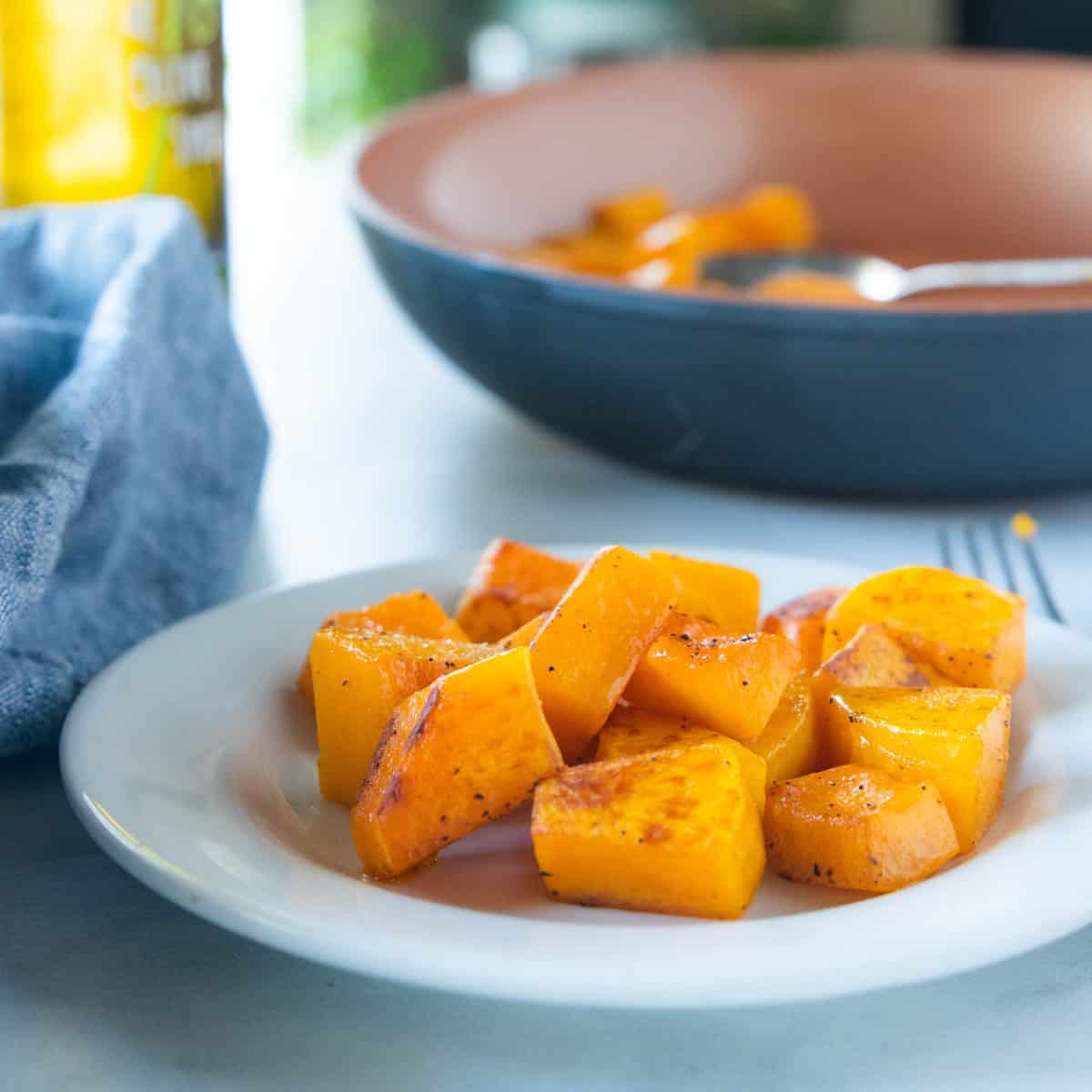 Sauteed butternut squash on a white plate with a fork next to the plate and a large serving bowl filled with sautéed squash behind the white plate.