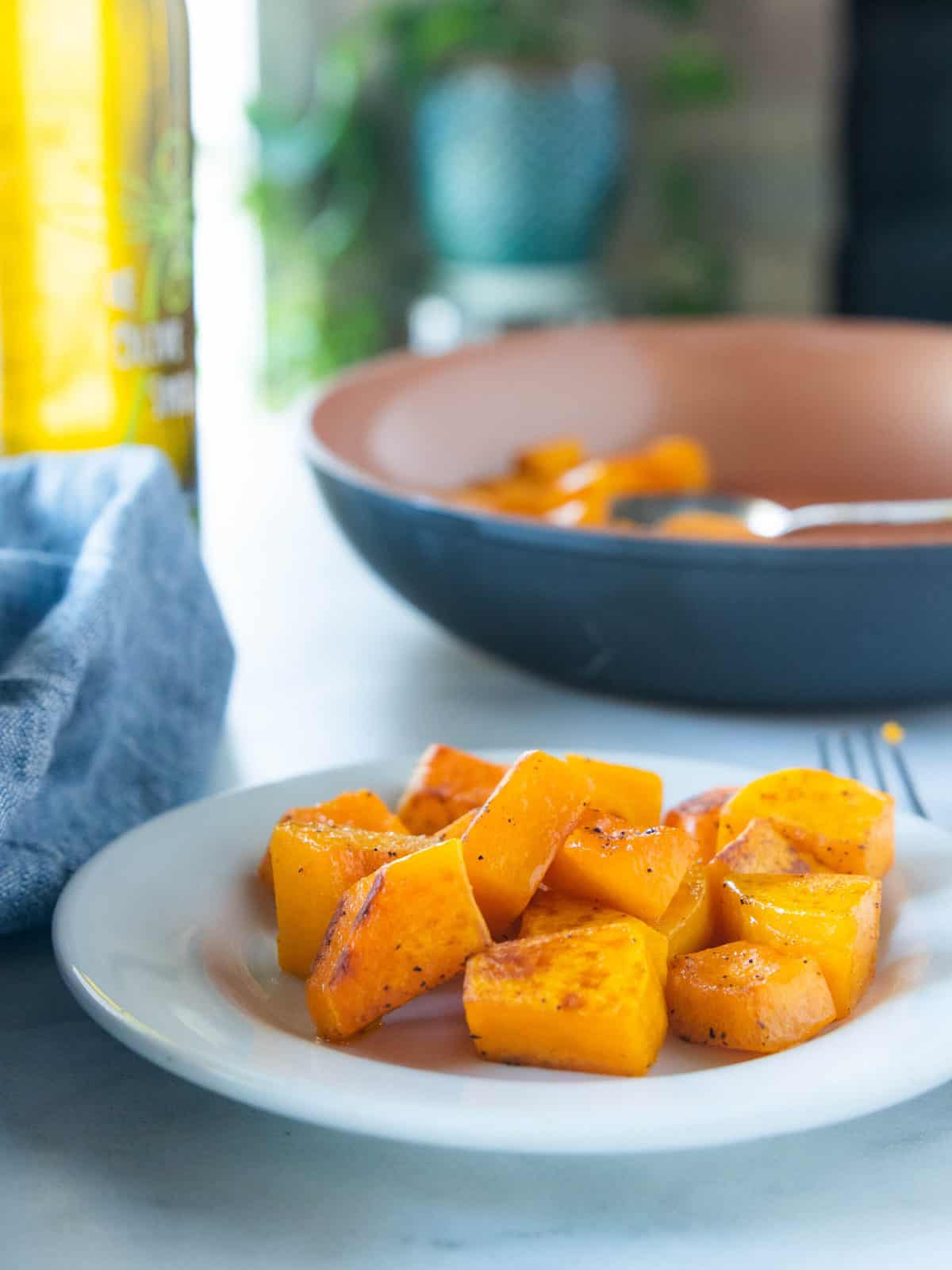 Sautéed butternut squash on a white plate with a fork next to the plate and a large serving bowl filled with sautéed squash behind the white plate.