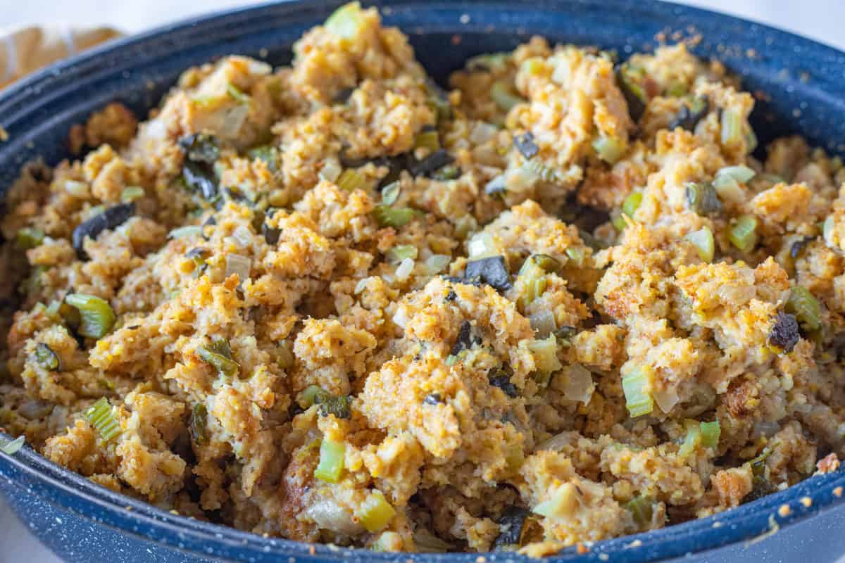 Easy Cornbread Stuffing being shown in a large blue roasting pan.