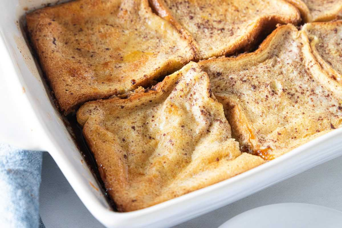 French toast casserole being shown in a white baking dish.