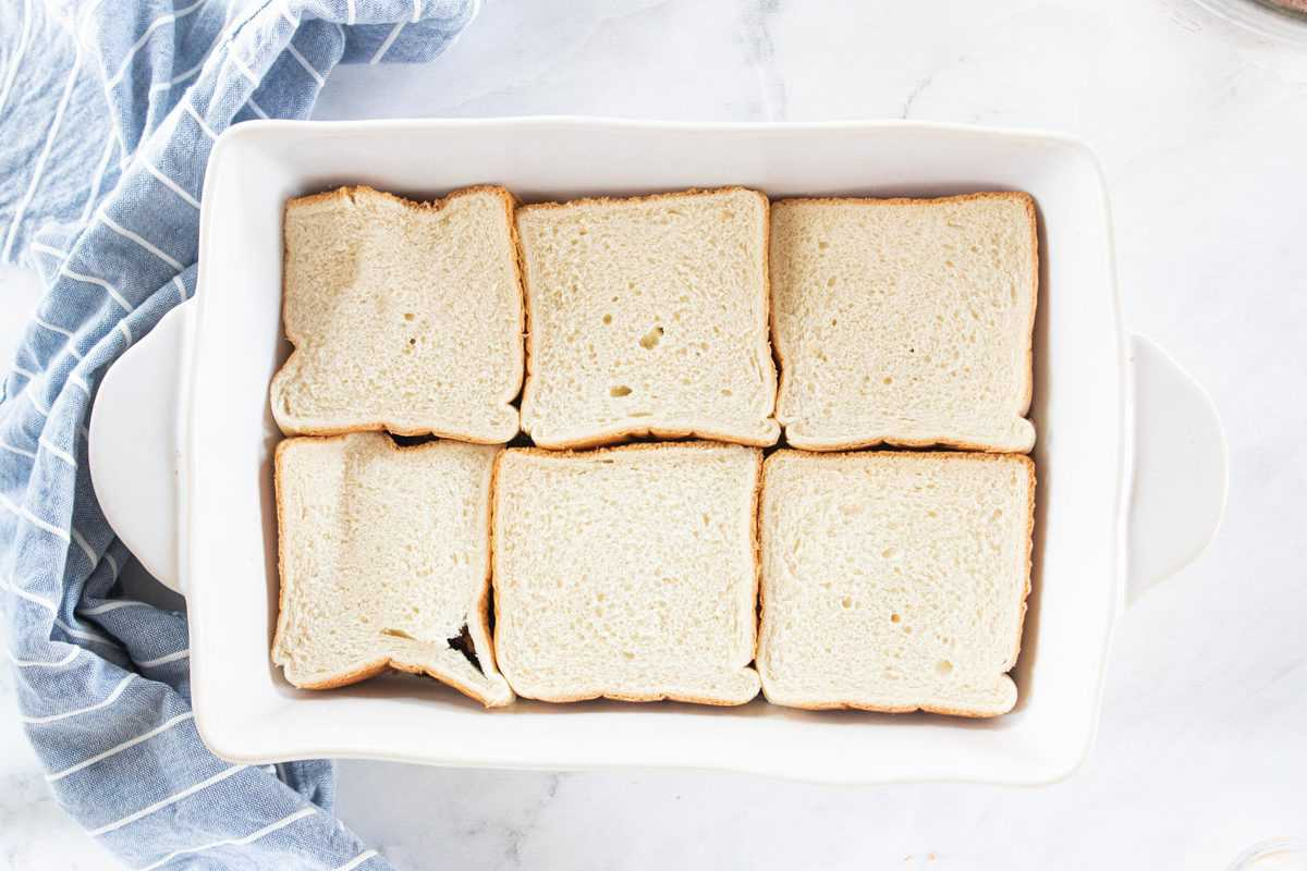 A white baking dish with slices of white bread layered on top of a brown sugar mixture being shown.