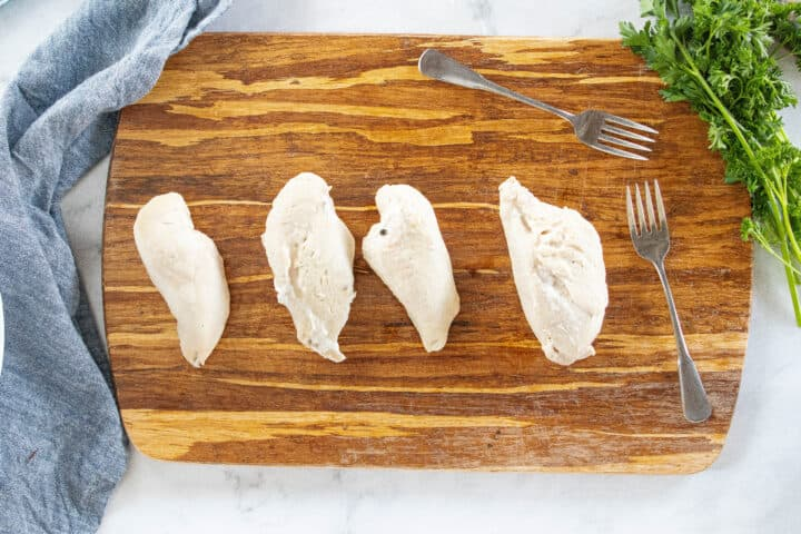 Four chicken breasts shown on a wooden cutting board with two forks on the board all on top of a countertop.