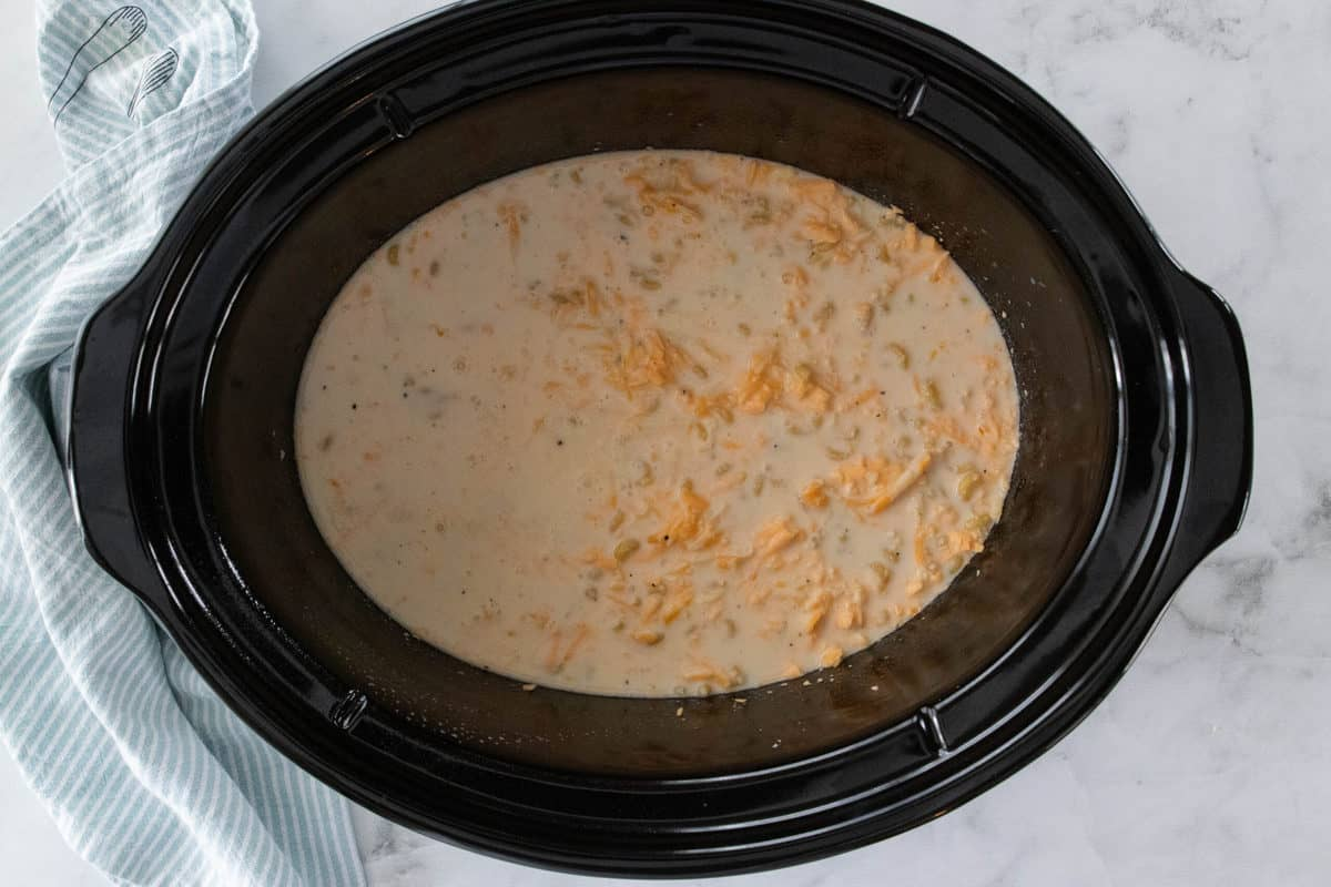 A crockpot insert shown filled with ingredients for Mac and cheese.