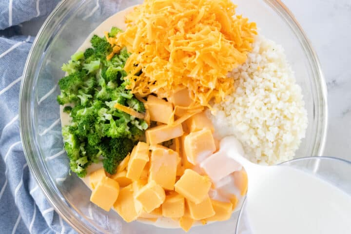 Broccoli, riced cauliflower, shredded cheese and chunks of cheese being shown in a glass mixing bowl with milk being poured into the bowl.