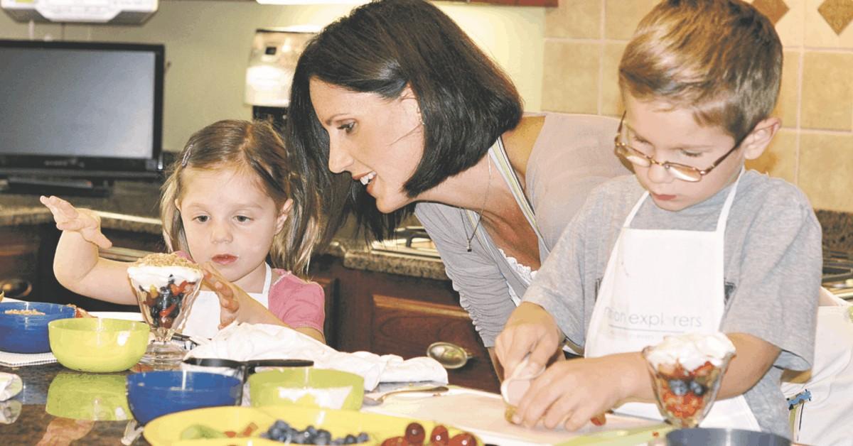 A parent and two preschoolers making yogurt parfaits.