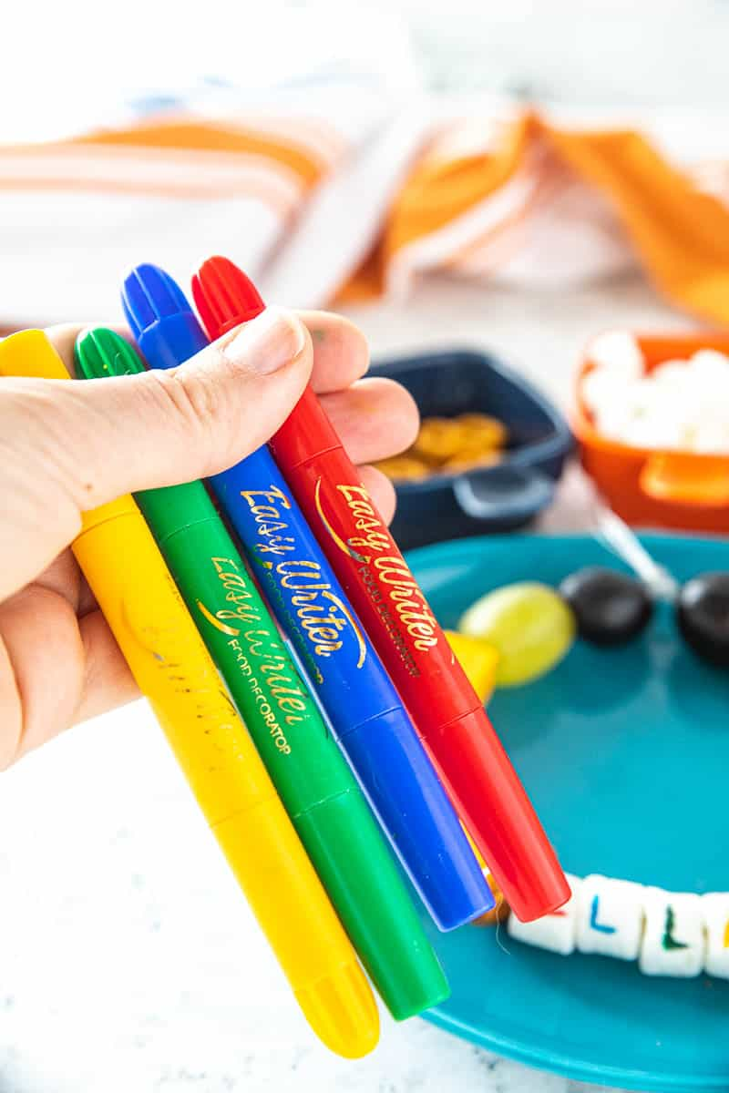A hand holding 4 edible markers.
