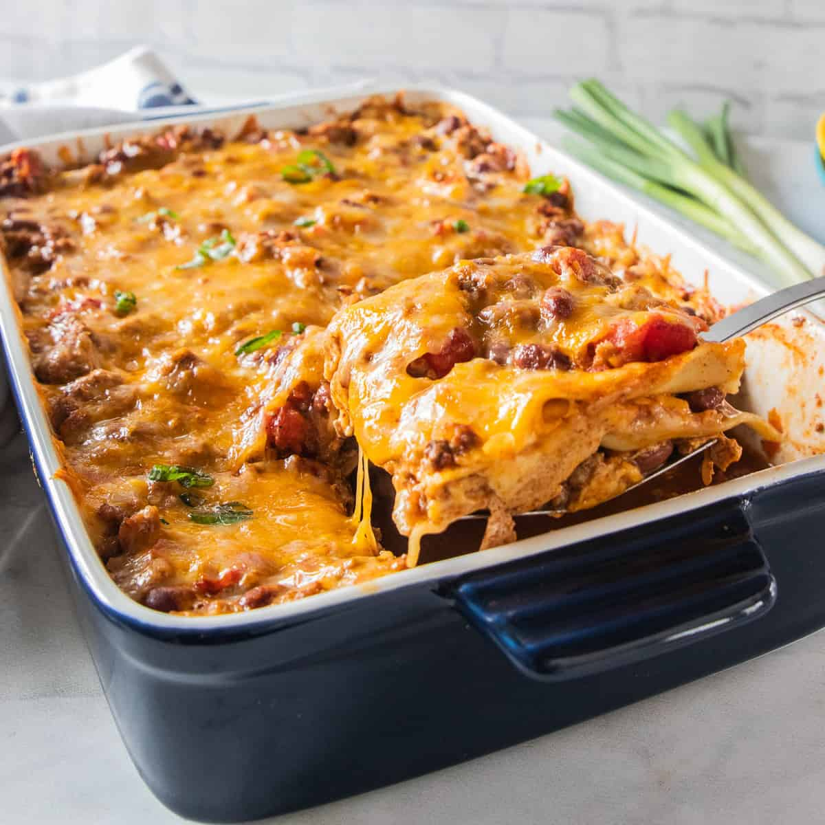 Chili lasagna being scooped from a baking dish.