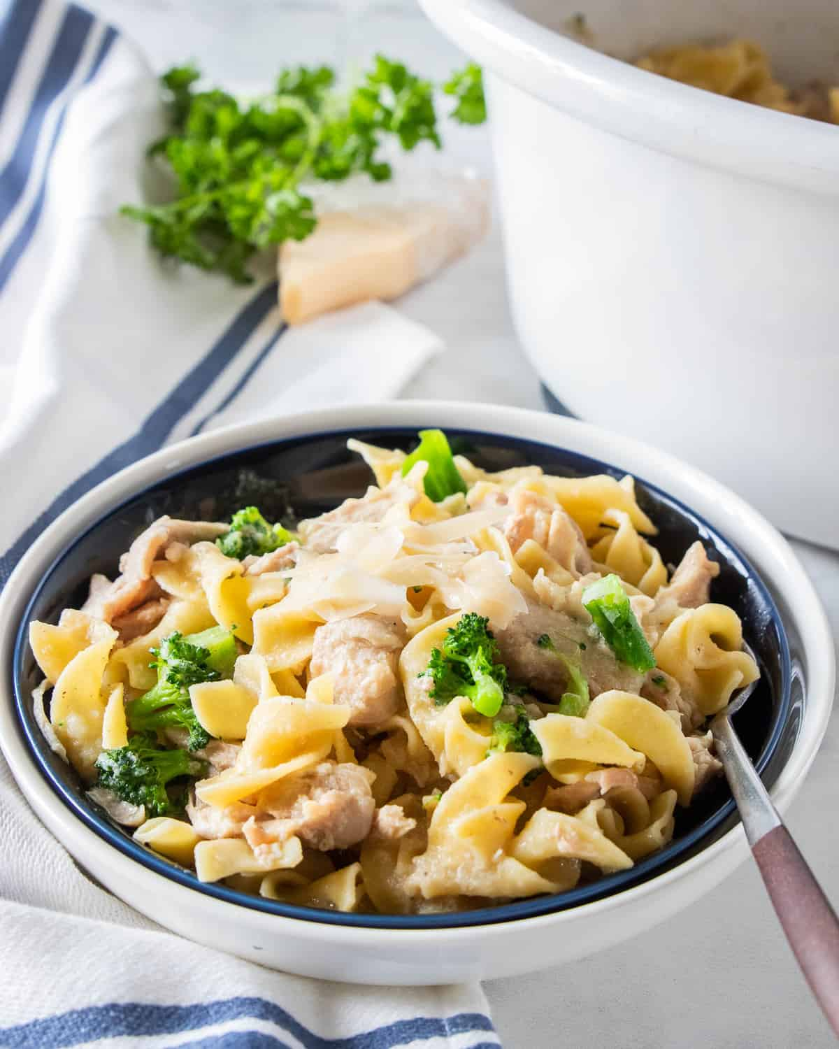 Crockpot chicken and noodles in a serving bowl with a fork.