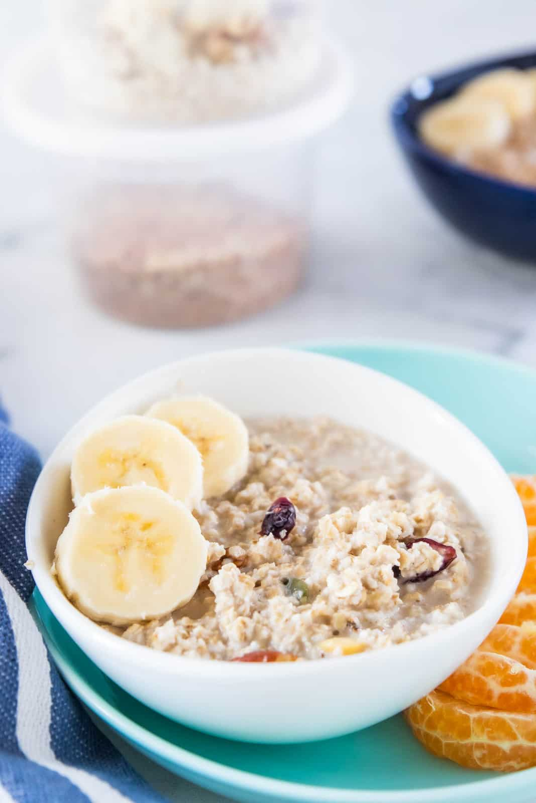 Oatmeal in a white bowl topped with slices of banana.