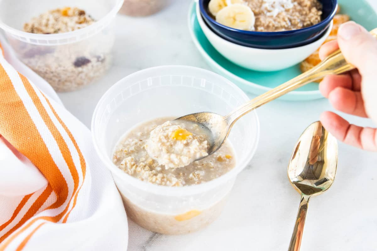 A spoon scooping a serving of oats from a container.