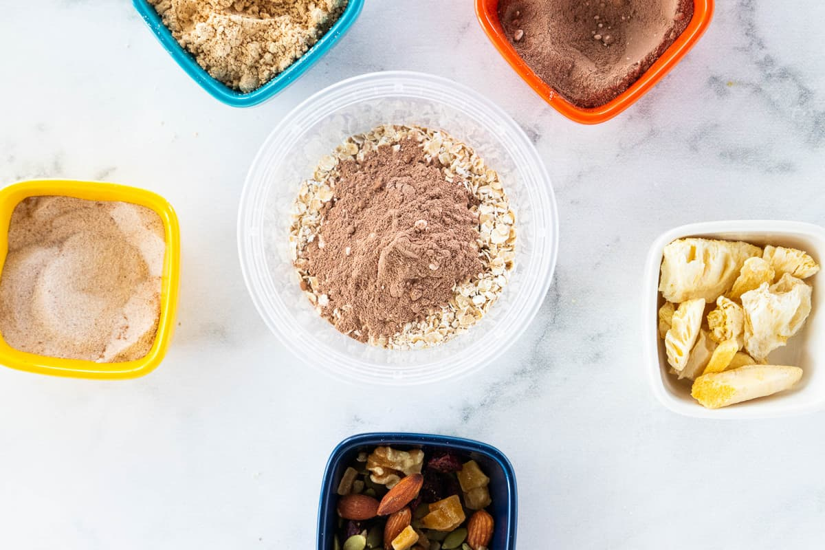 A container of chocolate oats surrounded by a variety of toppings