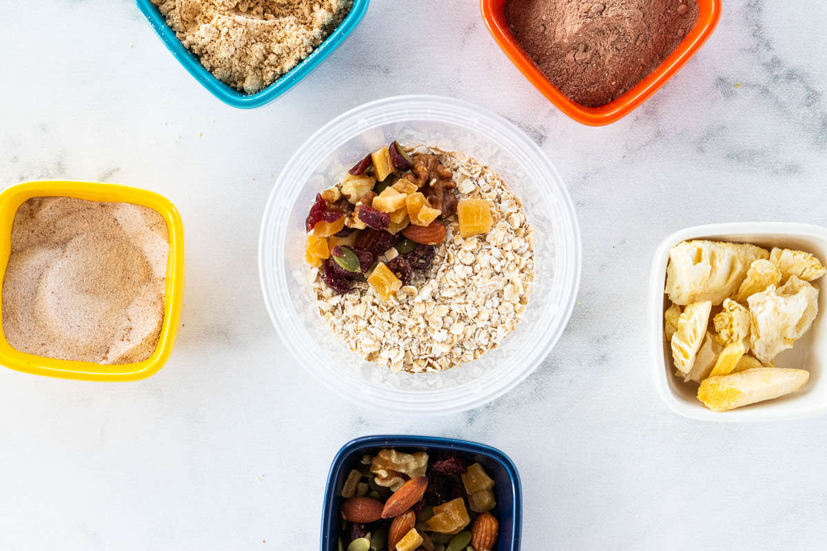 A container of oats with trail mix on top surrounded by a variety of toppings