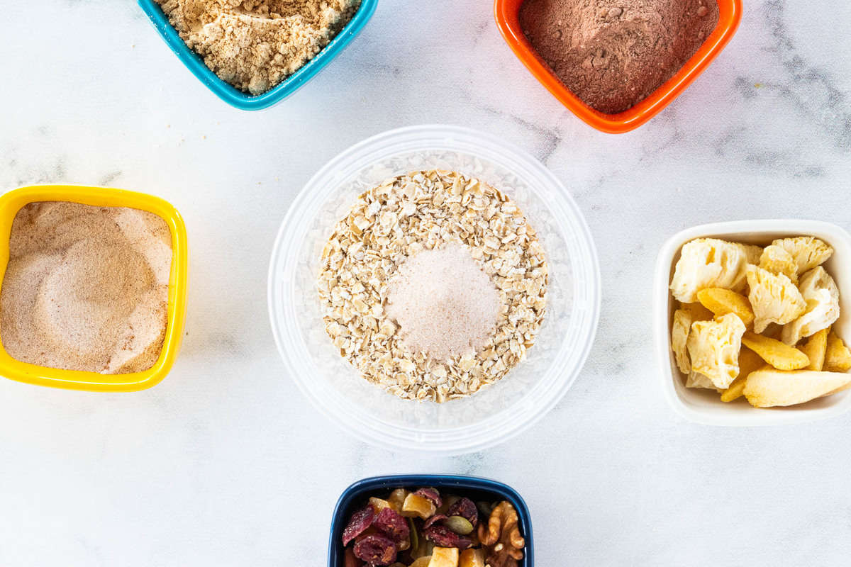 A container of oats surrounded by a variety of toppings