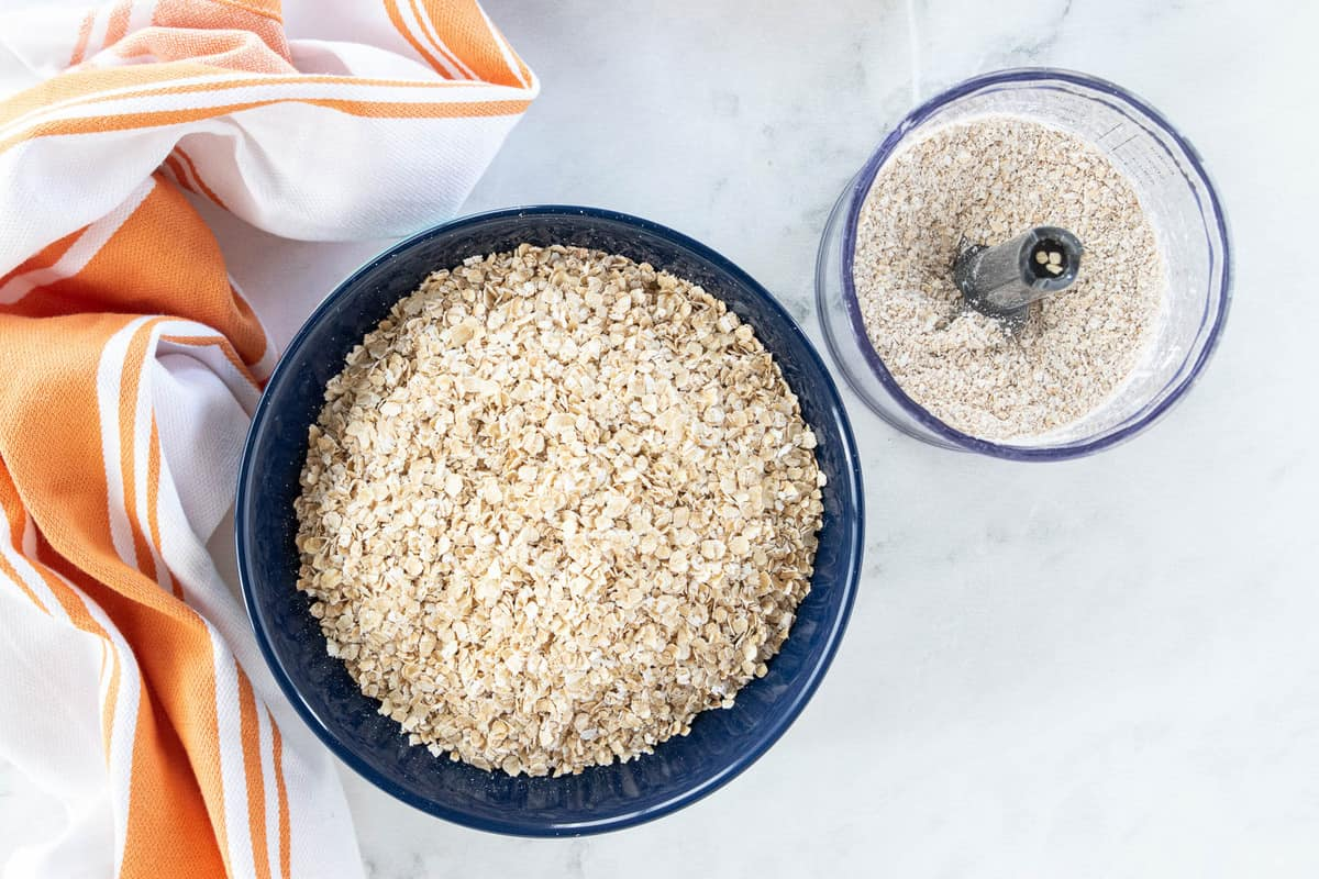 A bowl of oats and a small food processor filled with pureed oats.