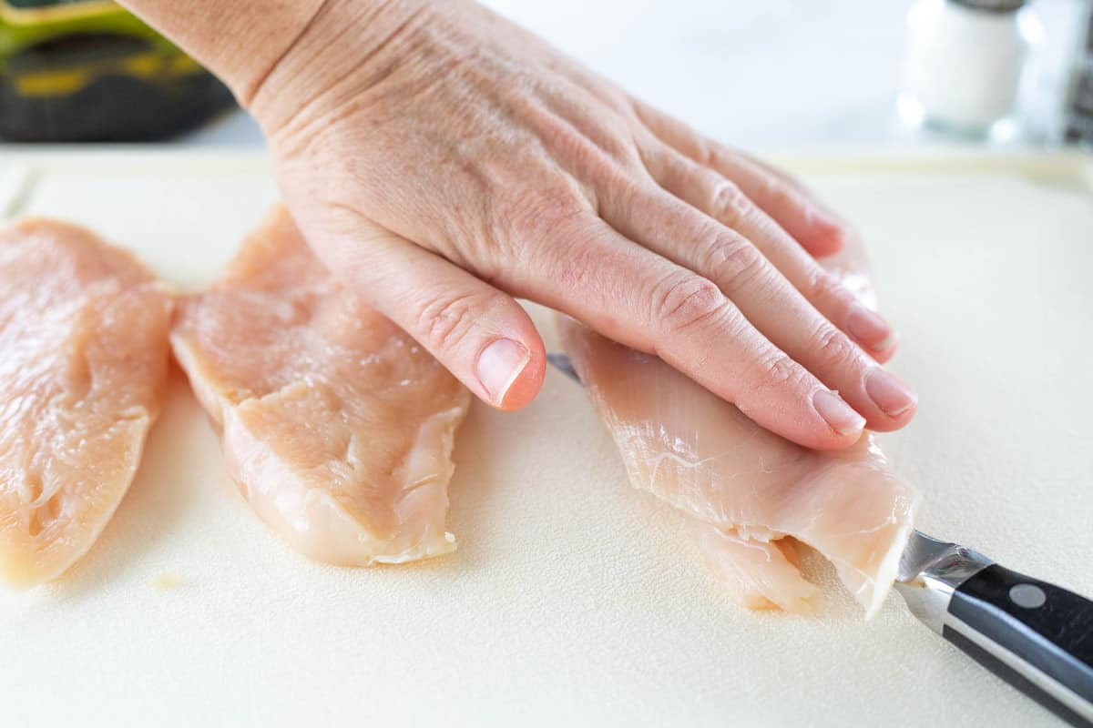 Chicken breasts shown being sliced in half on top of a cutting board with a knife.