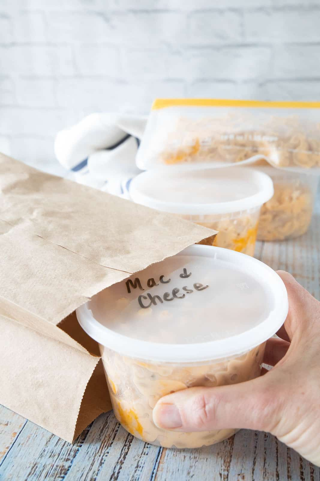 Cooked Mac & cheese in a container being placed by a hand into a brown paper bag.